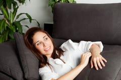Muchacha pensativa que se relaja en el sofá en casa Foto de archivo libre de regalías
