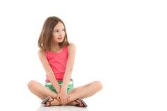 Muchacha pensativa que se sienta con las piernas cruzadas Imagen de archivo