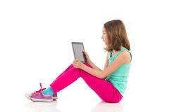 Muchacha pensativa que se sienta en el piso con una tableta digital Imagen de archivo libre de regalías