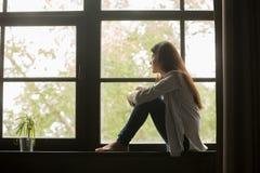 Muchacha pensativa que se sienta en las rodillas del abarcamiento del travesaño que miran windo Fotografía de archivo libre de regalías