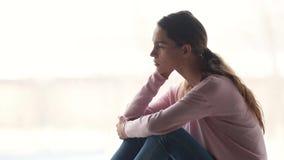 Muchacha pensativa pensativa que se sienta solamente mirando el reflejo lejos de pensamiento almacen de video