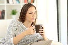 Muchacha pensativa que sostiene una taza de café en un sofá en casa Imagen de archivo