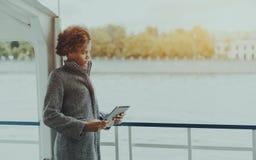 Muchacha pensativa rizada con la tableta digital en cubierta de la nave Imagen de archivo libre de regalías