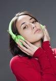 Muchacha pensativa 20s que escucha la música con el auricular Fotografía de archivo libre de regalías