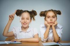 Muchacha pensativa y muchacha feliz que se sienta en el escritorio en gris Concepto de la escuela Fotos de archivo libres de regalías