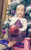 Muchacha pequeña y feliz que se divierte que adorna el árbol de navidad Fotos de archivo libres de regalías