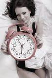 Muchacha perezosa atractiva que miente con el despertador en cama Foto de archivo