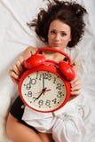 Muchacha perezosa atractiva que miente con el despertador rojo en cama Fotos de archivo libres de regalías