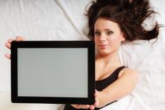 Muchacha perezosa atractiva que miente con el panel táctil de la tableta en cama Foto de archivo libre de regalías