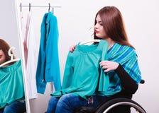 Muchacha perjudicada en la silla de ruedas que elige la ropa Imágenes de archivo libres de regalías