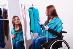 Muchacha perjudicada en la silla de ruedas que elige la ropa Foto de archivo libre de regalías