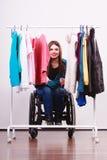 Muchacha perjudicada en la silla de ruedas que elige la ropa Imagenes de archivo