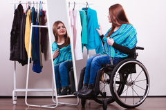 Muchacha perjudicada en la silla de ruedas que elige la ropa Foto de archivo