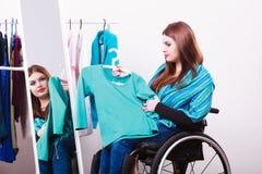 Muchacha perjudicada en la silla de ruedas que elige la ropa Fotos de archivo libres de regalías