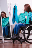 Muchacha perjudicada en la silla de ruedas que elige la ropa Fotografía de archivo
