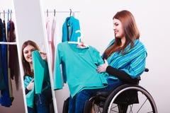 Muchacha perjudicada en la silla de ruedas que elige la ropa Fotos de archivo