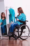 Muchacha perjudicada en la silla de ruedas que elige la ropa Imagen de archivo libre de regalías