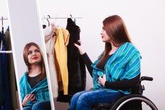 Muchacha perjudicada en la silla de ruedas que elige la ropa Imagen de archivo