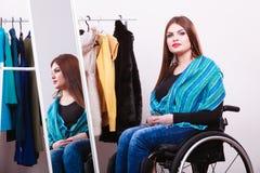 Muchacha perjudicada en la silla de ruedas que elige la ropa Fotografía de archivo libre de regalías