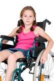Muchacha perjudicada joven en una silla de ruedas Imagen de archivo libre de regalías