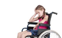 Muchacha perjudicada muy triste en un sillón de ruedas Fotografía de archivo libre de regalías