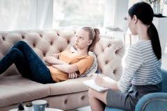 Muchacha pesimista que miente en el sofá durante la cita psicológica Fotografía de archivo libre de regalías