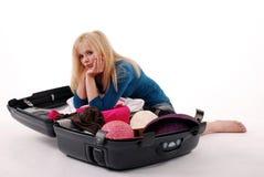 Muchacha a pila de discos sus cosas en una maleta Imagen de archivo libre de regalías