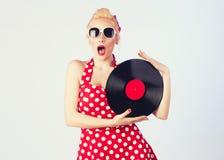 Muchacha Pin-para arriba en el vestido del vintage que lleva a cabo un disco de vinilo Foto de archivo