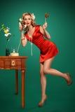 Muchacha Pin-para arriba que habla en el teléfono retro y que sostiene una piruleta Fotografía de archivo libre de regalías