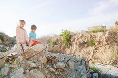 Muchacha pobre del muchacho de dos niños del refugiado en la construcción de las ruinas destruida por ataque aéreo imagenes de archivo