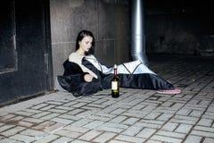 Muchacha pobre joven que se sienta en la pared sucia en piso con la botella de vid, alcohólico pobre del refugiado, desamparados  Imágenes de archivo libres de regalías