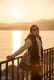 Muchacha por el mar en puesta del sol Fotos de archivo