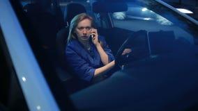 Muchacha por la tarde que habla en el teléfono mientras que se sienta en el coche almacen de metraje de vídeo