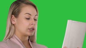 Muchacha positiva alegre que hace la llamada video en una pantalla verde, llave de la croma almacen de metraje de vídeo