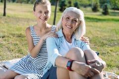 Muchacha positiva alegre que sostiene sus hombros de las abuelas Imagen de archivo libre de regalías