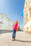 Muchacha positiva con el globo azul del vuelo en el cielo Imágenes de archivo libres de regalías