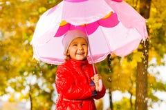 Muchacha positiva con el paraguas que se coloca debajo de la lluvia Foto de archivo