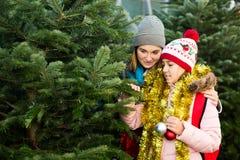 Muchacha positiva con la mamá que elige el árbol del ` s del Año Nuevo Fotografía de archivo