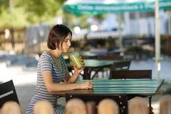 Muchacha positiva con un smoothie Mujer sonriente que se sienta en el fondo borroso del café Al aire libre concepto del café Copi Imagen de archivo libre de regalías