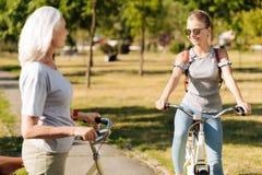 Muchacha positiva del adolescente que goza montando la bicicleta en el parque Imagen de archivo