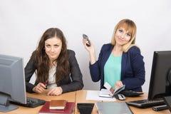 Muchacha positiva en la oficina con un teléfono en su mano cerca de las contrapartes negativas foto de archivo