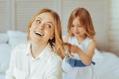Muchacha positiva encantada que se sostiene el pelo de las mamáes Imagen de archivo