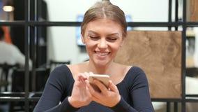 Muchacha positiva que usa Smartphone, retrato en oficina