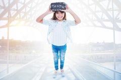 muchacha Pre-adolescente en las auriculares de VR que se colocan en el puente Imágenes de archivo libres de regalías