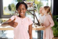 Muchacha pre-adolescente encantadora que muestra los pulgares para arriba Imagen de archivo libre de regalías