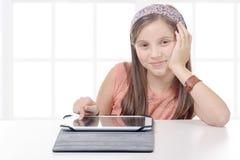 Muchacha pre-adolescente hermosa con una tableta Imágenes de archivo libres de regalías