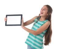 Muchacha pre-adolescente hermosa que ríe con una tableta Foto de archivo