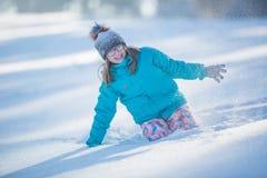 Muchacha Pre-adolescente joven feliz en la ropa caliente que juega con nieve Imágenes de archivo libres de regalías