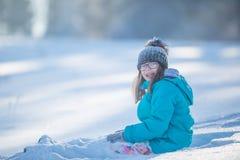 Muchacha Pre-adolescente joven feliz en la ropa caliente que juega con nieve Fotografía de archivo