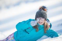 Muchacha Pre-adolescente joven feliz en la ropa caliente que juega con nieve Imagen de archivo libre de regalías